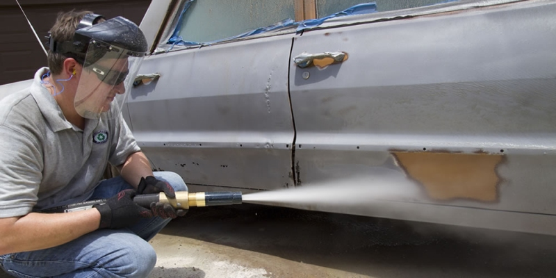 Stripping paint from a car with sand blasting